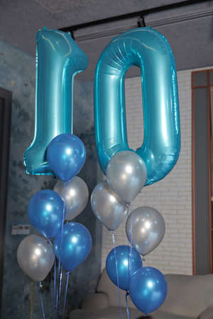 10 year old blue balloon. Ten-year-old blue balloon. White and blue balloons. Word 10 written with helium blue balloons .