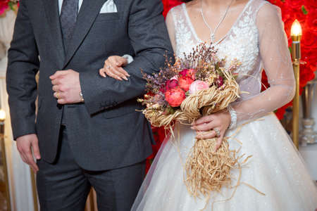 dried coral reach pink wheat cotton flower bridal bouquet . The bride entered the groom's armpit and held a bouquet of flowers Imagens