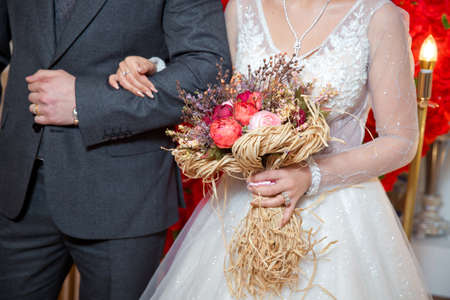 dried coral reach pink wheat cotton flower bridal bouquet . The bride entered the groom's armpit and held a bouquet of flowers Banque d'images