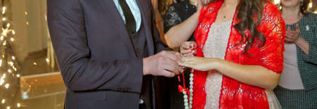 room Dresses the Ring for the Bride, close-up. Newlyweds exchange rings, groom puts the ring on the bride's hand in marriage registry office . The brides is wearing a ring on the bride's hand . Banque d'images