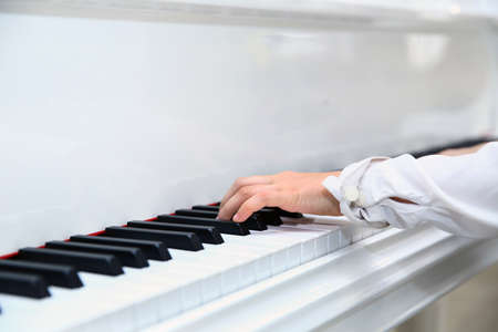 Little boy playing the piano at home . White piano .