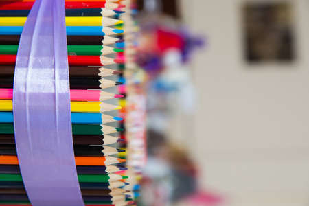 Colorful colored pencils on blurred bokeh background . Colored pencils arranged in a row and in a circle . close up of colorful set wooden color pencil in isolated black and blur background. Banco de Imagens