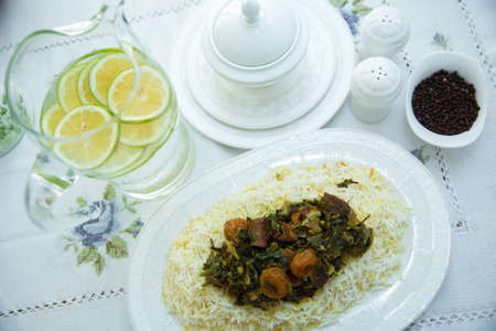Rice in a white plate. Sliced lemon . A bowl of white ceramic salt and pepper. Shah pilaf. Khan pilaf . Black pepper in a white ceramic pot . There is meat, greens and plum chestnuts on the pilaf. Zdjęcie Seryjne