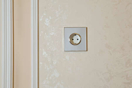 Electrical switch and plug on wall . Realistic white socket. plug white shadow rectangle wall . Green power eco white plug on white wall . Power socket in concrete wall Foto de archivo