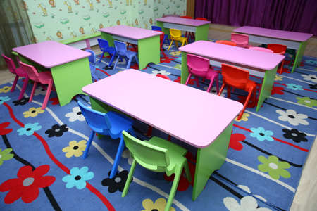 refectory of a school for children with chairs and tables without people . Interior of a spacious kindergarten room with small children tables and chairs.