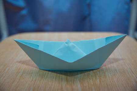 Origami paper ship . Leadership concept with blue paper ship leading among wooden . Blue paper boat on wooden background .