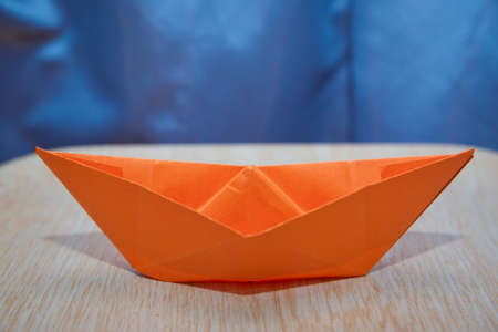 Origami paper ship . Leadership concept with orange paper ship leading among wooden . Orange paper boat on wooden and blue background .
