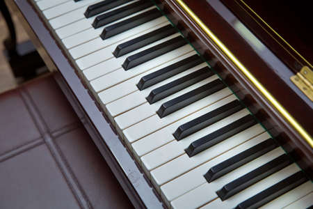 Defocused classic piano keyboard in white and brown colors . piano presses . Piano keys close up. Musical instrument . Select focus and soft focus.Close-up of a wooden piano .