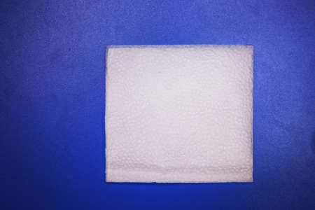 White Square Bar Napkin Isolated on blue Background . Blank paper napkin isolated on blue background with copy space . White napkin on blue background, many views of white napkins, blank mockup files.
