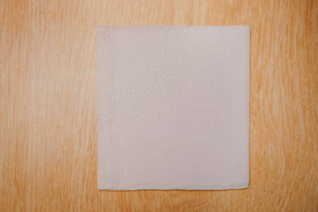 White Square Bar Napkin Isolated on wooden Background . Blank paper napkin on wooden background with copy space . White napkin on wooden background, many views of white napkins, blank mockup files .