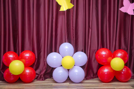 Red, white, yellow flower balloon. Red curtain . Flower made from balloons isolated on Red curtain background. Stock Photo