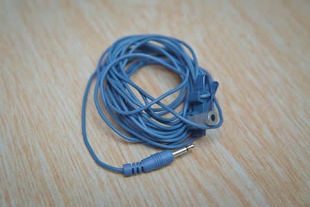 Blue Microphone and headphone splitter cable . Audio Mini Jack Cable for microphone isolated on wooden background . Stock Photo