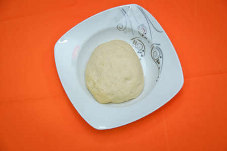 The dough is on a white plate on an orange background . Raw dough lying on the plate on a white background. A piece of dough for bread baking Stock Photo