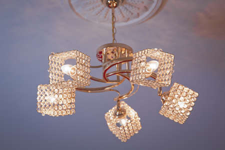 Chandelier Lamp beautiful luxury expensive chandelier hanging under ceiling . The lamp in the beautiful room . Brass chandelier with crystal. beautiful crystal chandelier in a room .