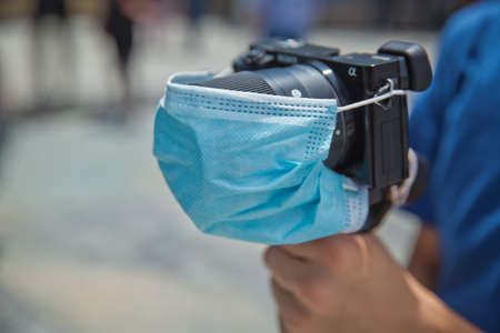 Azerbaijan Baku : 26.06.2020 . Man holding gimbal stabilizer camera outdoor. A blue mask is attached to the camera lens. The camera is protected by COVID-19
