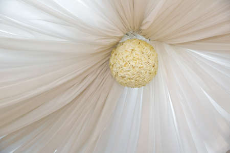 White rose ball on the ceiling . There is a white curtain on the ceiling . Stock Photo