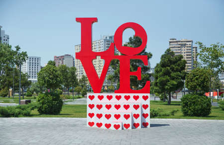 Azerbaijan Baku 7.07.20202 . A brightly colored, outdoor sculpture in a public park in Azerbaijan consists of red letters spelling LOVE . Love red letters in green tropical park, outdoor decor photo.