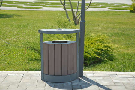 Brown garbage bin inside a wooden enclosure at a park. copy space on the left . Rubbish box in the park . A wooden urn and a comfortable empty park bench . Stock Photo