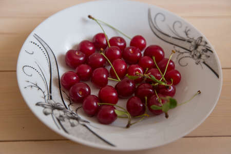 On a wooden background in a cherry white plate . Fresh cherry on plate on wooden background. fresh ripe cherries. sweet cherries.