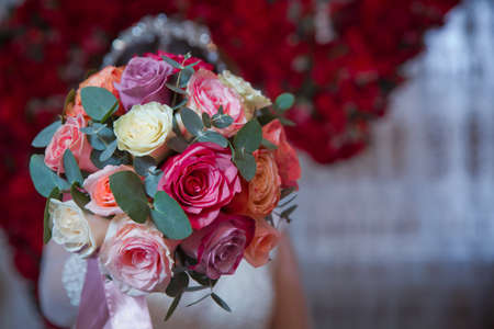 The brides dress was white . The bride is holding a multi-colored wedding bouquet .