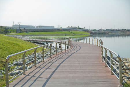 An oval bridge from iron and wood on the edge of the lake . Boyukshor Lake in Baku Azerbaijan . According to geological data, the average depth of the water in the lake is 3.40-3.95 meters .