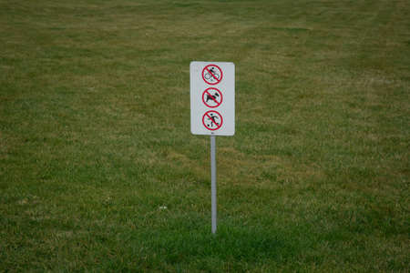 Do not walk the dog on the grass . Do not walk on the grass sign in the park . You can't ride a bike Bicycles on the grass and play football . Prohibition sign in the green garden.