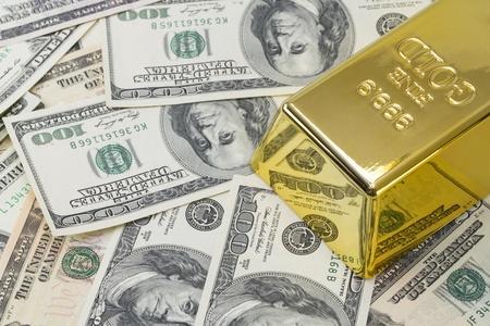1000 grams or kilo golden bar on background of hundred dollar banknotes