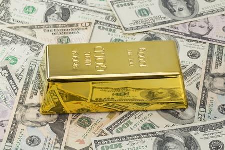 grams: 1000 grams or kilo golden bar or ingot on background of hundred dollar banknotes