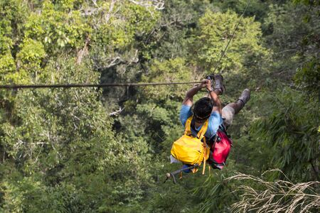 tarzan: A man ziplines through the forest in Lao Stock Photo