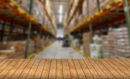 empty warehouse: Empty wood table top or shelf on blurred warehouse background - can montage or display your products