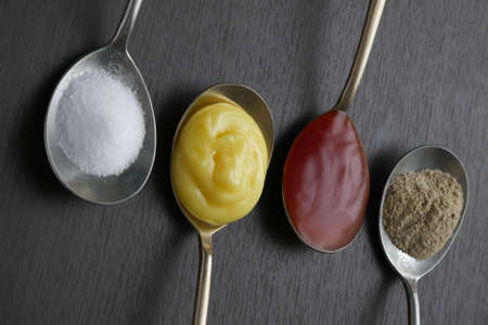 wholegrain mustard: Flat lay, on top, Variety of condiments on vintage spoons on wood background, tomato sauce, Salt, pepper, dressing