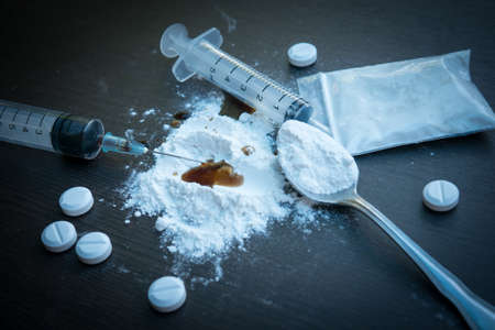 heroin: Drug syringe and cooked heroin on spoon