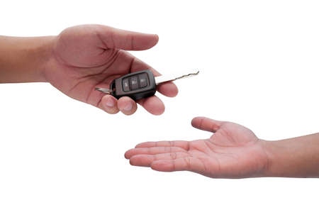 Male hand holding a car key and handing it over to another person isolated,