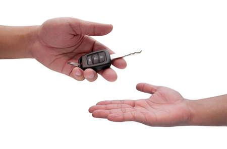Mannelijke hand die een autosleutel en af te voeren naar een andere persoon geïsoleerd,
