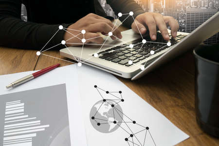business documents on office table with smart phone and digital tablet and graph business with social network diagram and man working in the background Stock Photo