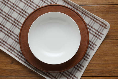 grunge silverware: white plate and fork on old wooden table with  checked tablecloth and copyspace, top view