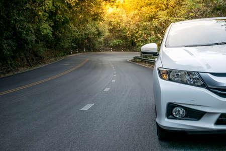 Cierre al frente de aparcamiento nuevo coche blanco en la carretera de asfalto de carreteras, unidad de la puesta del sol, luz de bengala Foto de archivo - 52267128