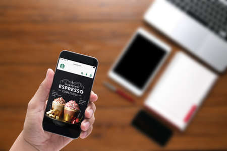 Bangkok, Thailand - Feb 5, 2015 : A man hand holding iphone with Starbucks menu web page on screen, coffee