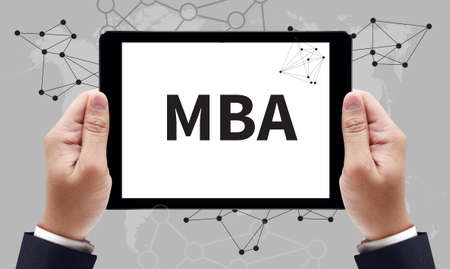 mba: MBA sign on tablet pc screen held by businessman hands - online MBA concept, top view