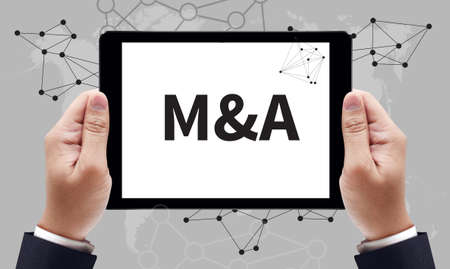 company ownership: M&A (Merger and Acquisition) sign on tablet pc screen held by businessman hands - online MBA concept, top view