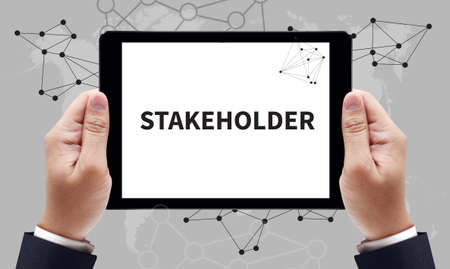 STAKEHOLDER, sign on tablet pc screen held by businessman hands - online MBA concept, top view Stock Photo