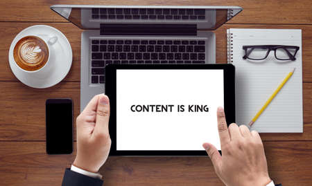 news values: CONTENT IS KING, message on tablet pc screen held by businessman hands - concept, top view computer, phone ,coffee, Warm tone Stock Photo