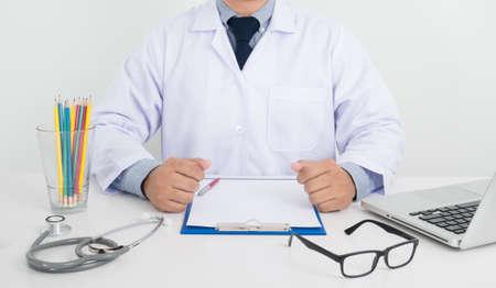 medical clipboard: doctor sitting at his desk, medical equipment and desktop on background, medical records on a blank sheet, Medical clipboard, laptop