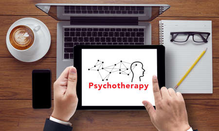 sioux: psychotherapy message on tablet pc screen held by businessman hands - concept, top view computer, phone ,coffee, Warm tone