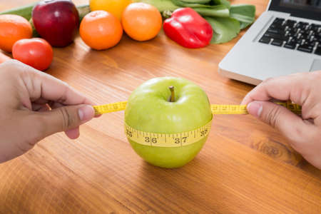 lap top: Nutritionist measuring an apple with measuring tape, dieting and weight loss concept, lap top