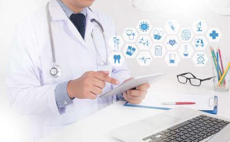 Close-up van een mannelijke arts in scrubs met behulp van digitale tablet. Geneeskunde arts hand werken met moderne computer interface als medische concept