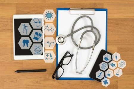 Equipos médicos: estetoscopio gris y la tableta, vista desde arriba de escritorio, interfaz como concepto médico