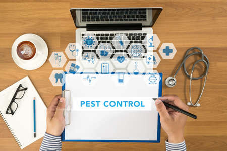disease prevention: Doctor writing medical records on a blank sheet and holding a clipboard, medical equipment and desktop on background, top view, coffee, Pest Control