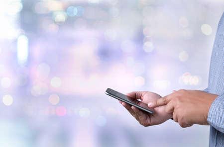 telefono caricatura: persona que tenga un teléfono inteligente en el fondo del paisaje urbano borrosa