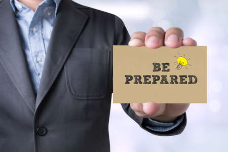 be prepared: Businessman BE PREPARED message on the card shown on blurred city background,holding empty card